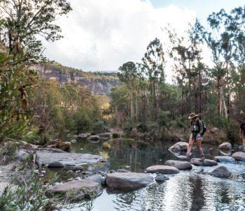 tourist crossing boulder stewn carnarvon creek